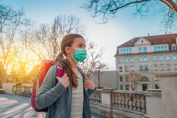 a school-aged girl walking outside with her backpack on and a surgical mask over her mouth and nose